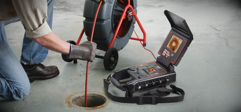 Man using video inspection tools to diagnose sewer pipe issues.